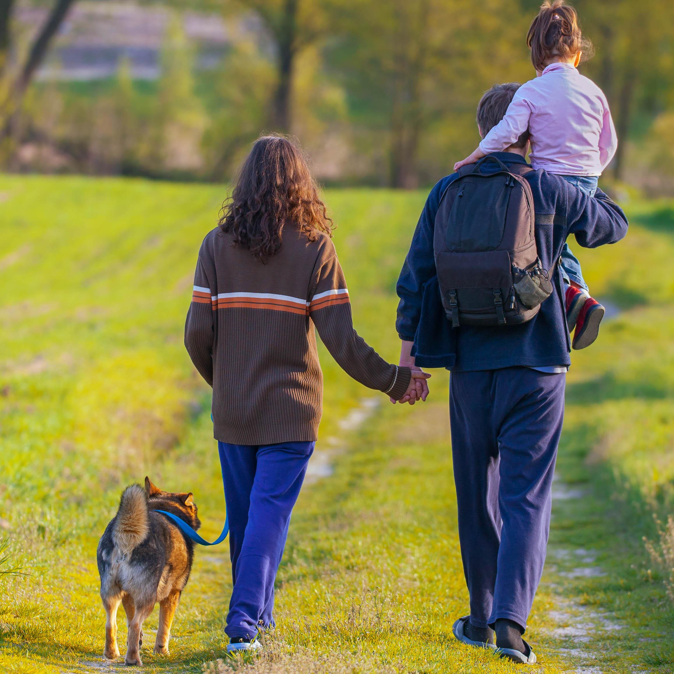 Eine Familie auf einem Spaziergang mit Hund