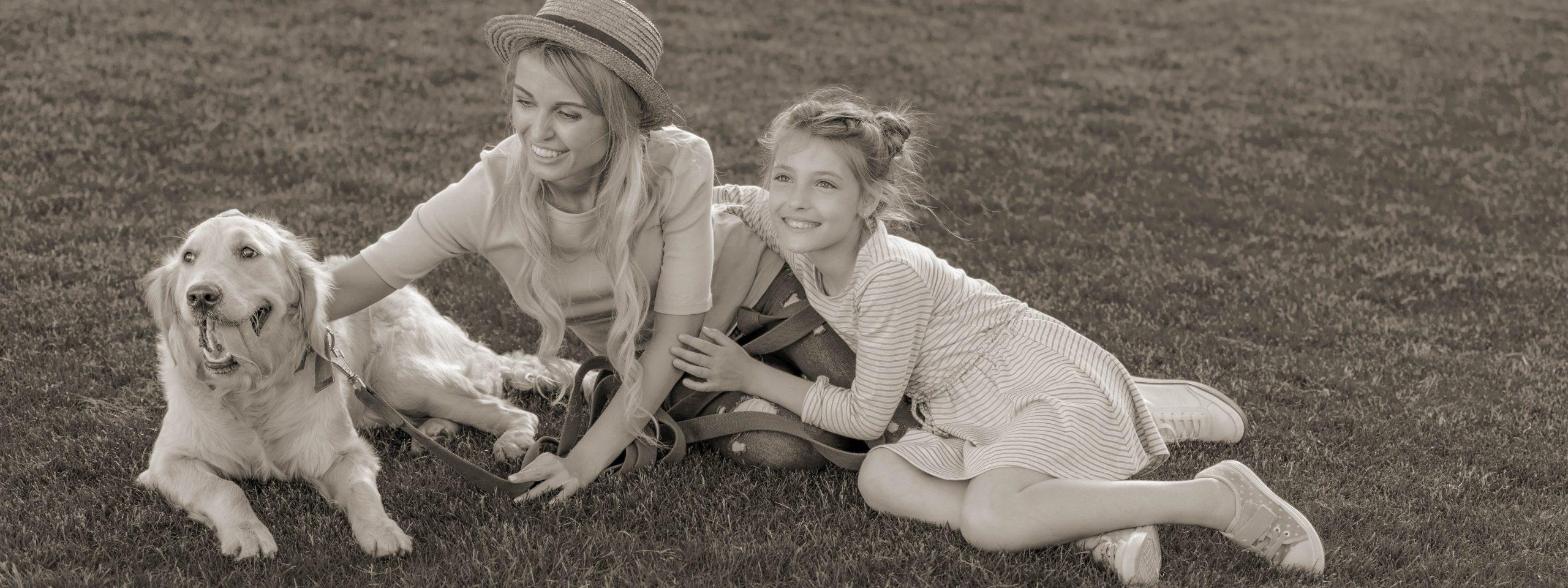 Mutter liegt mit Tochter und Golden strahlend auf einer Wiese