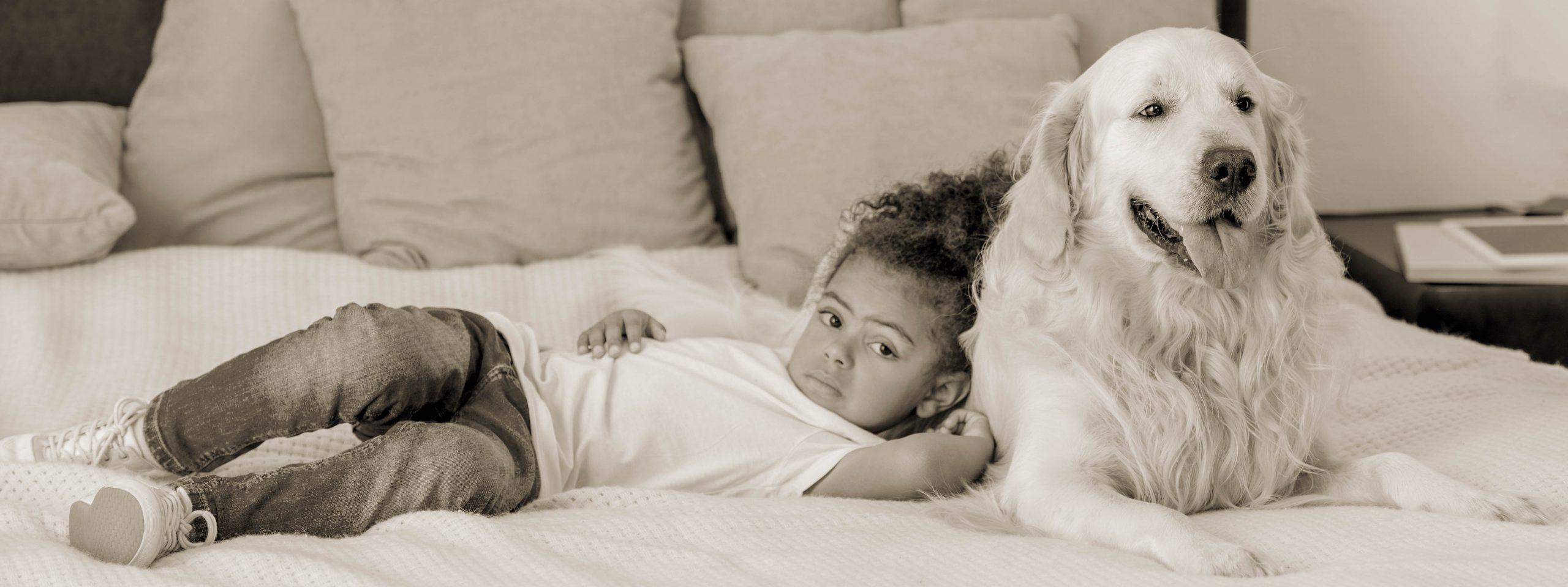 Ein Kind liegt mit einem Golden Retriever auf dem Bett