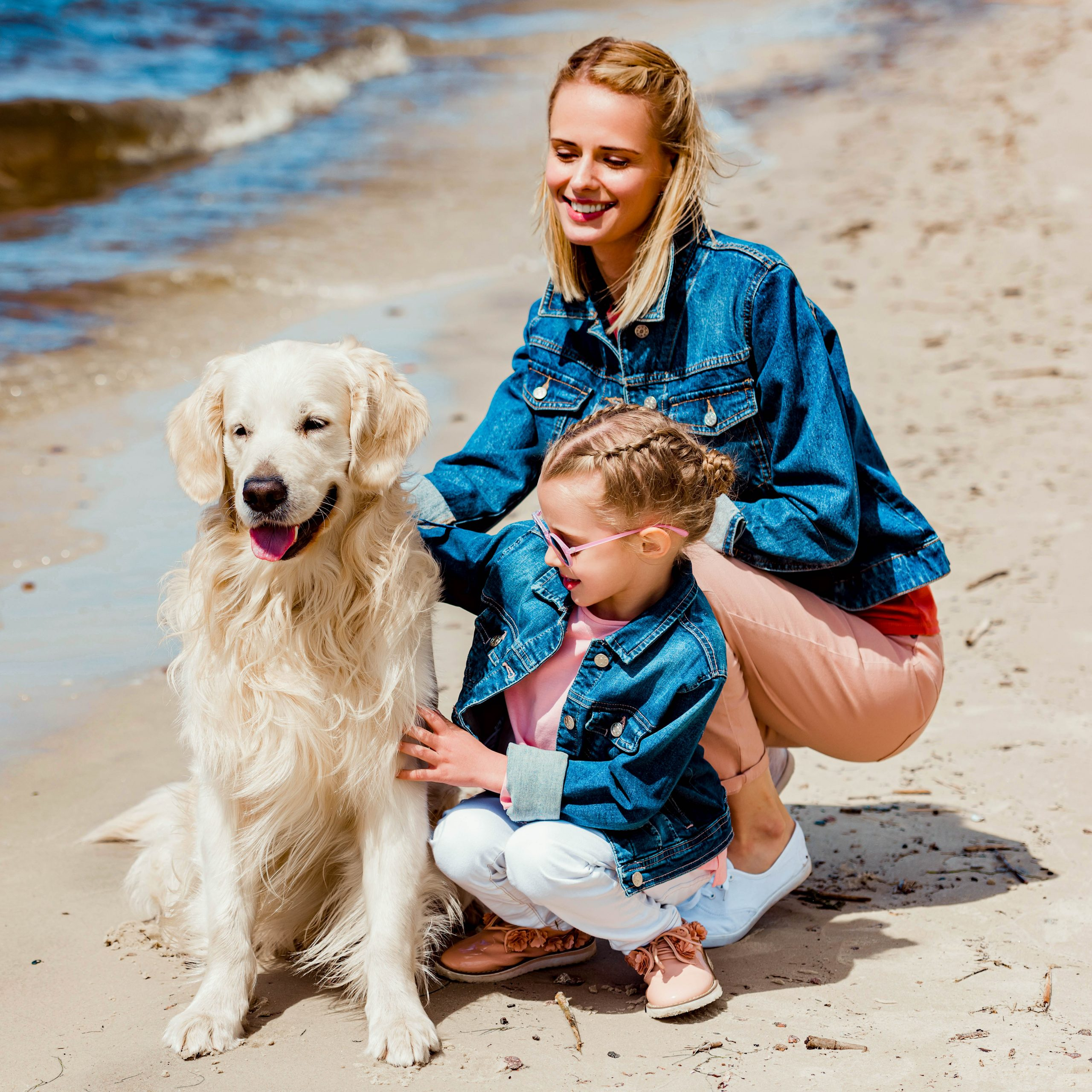Mutter mit Tochter am Meer mit Ihrem Hund