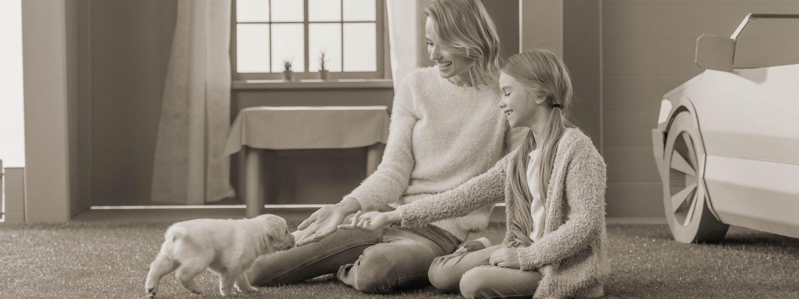 Mutter sitzt mit der Tochter am Boden und locken einen Welpen zu sich