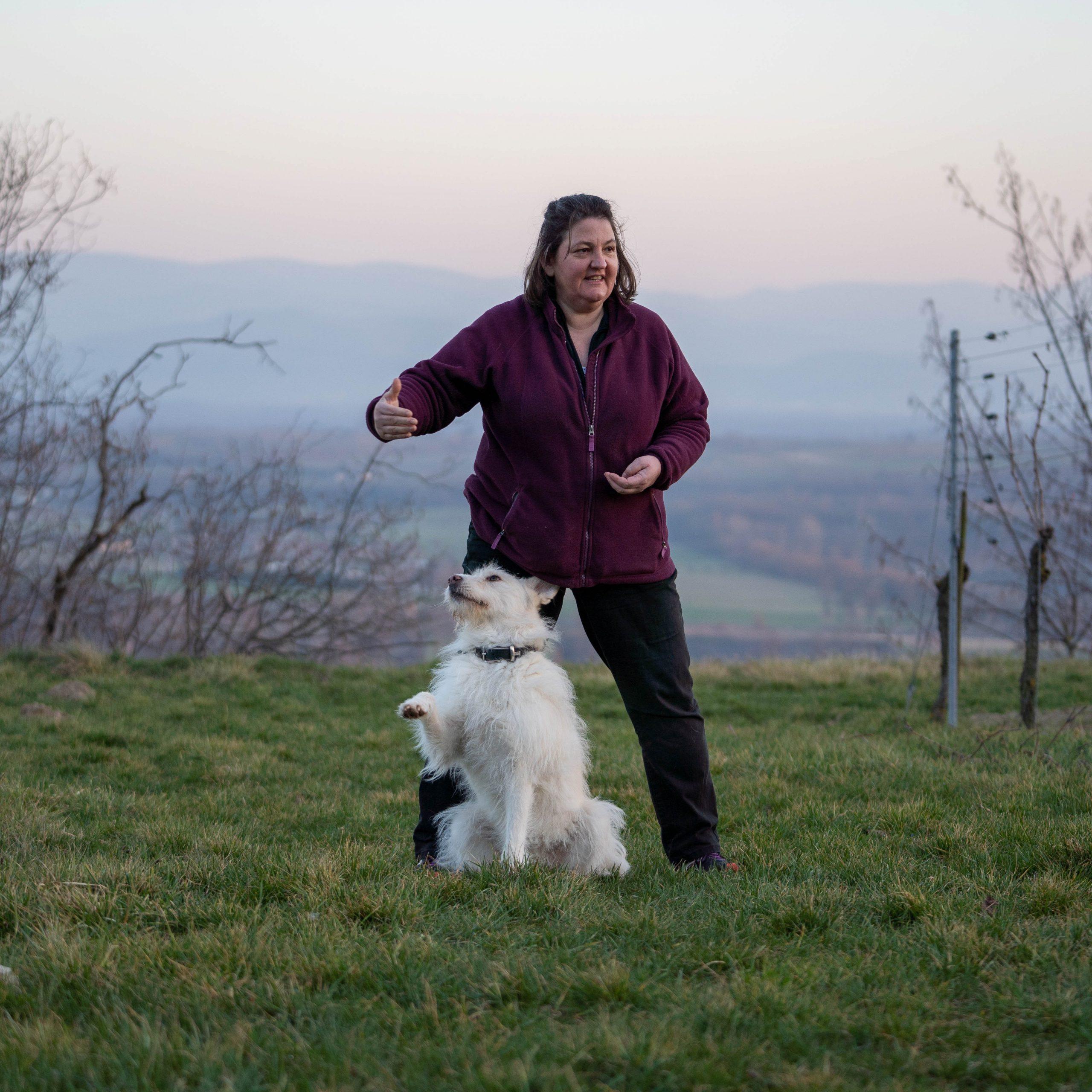 Frau mit weißem Hund auf einer Wiese
