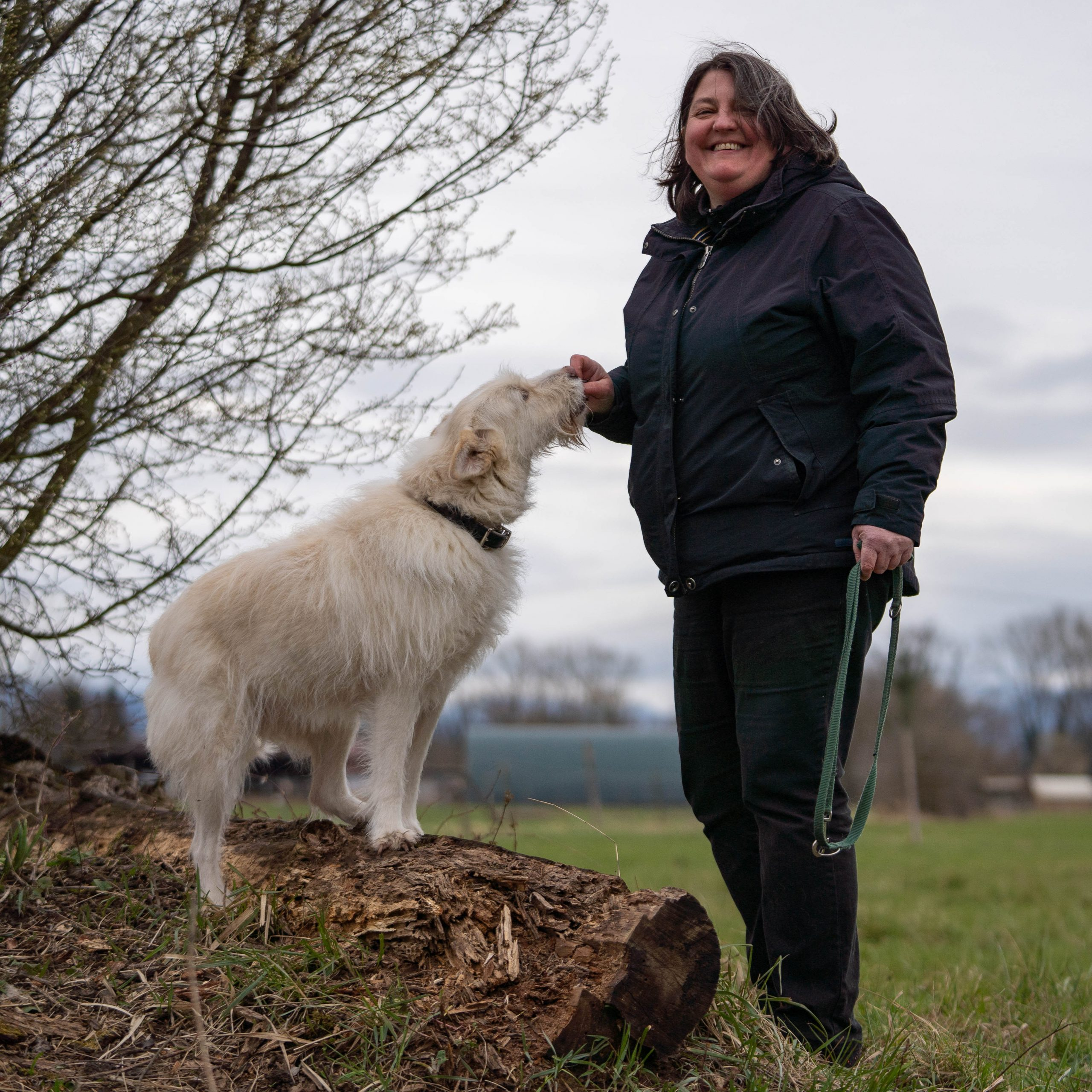 Susanne Allgeier übt mit einem weißen Hund Sitz
