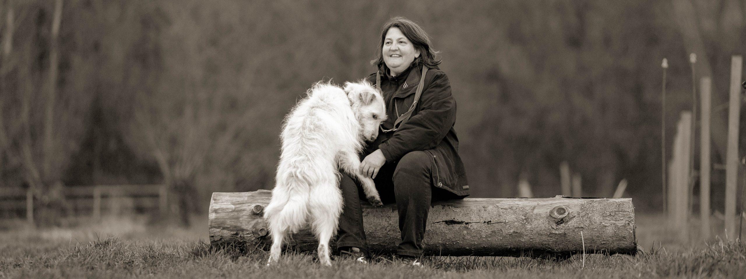 Susanne Allgeier sitzt auf einem Baumstamm, ihre Hündin lehnt sich an sie an