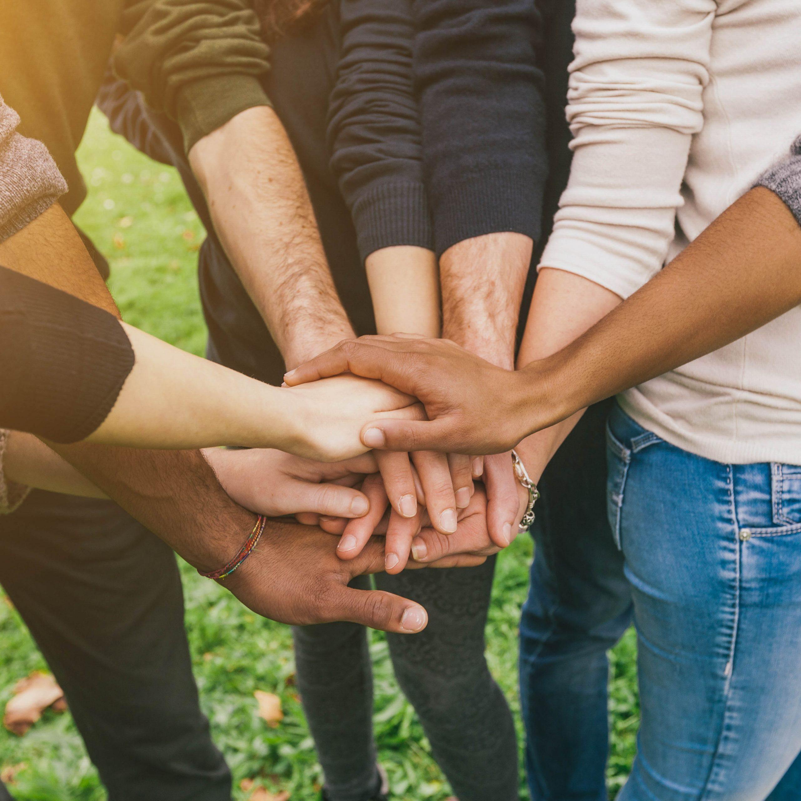 Menschen stehen im Kreis und halten ihre Hände zusammen