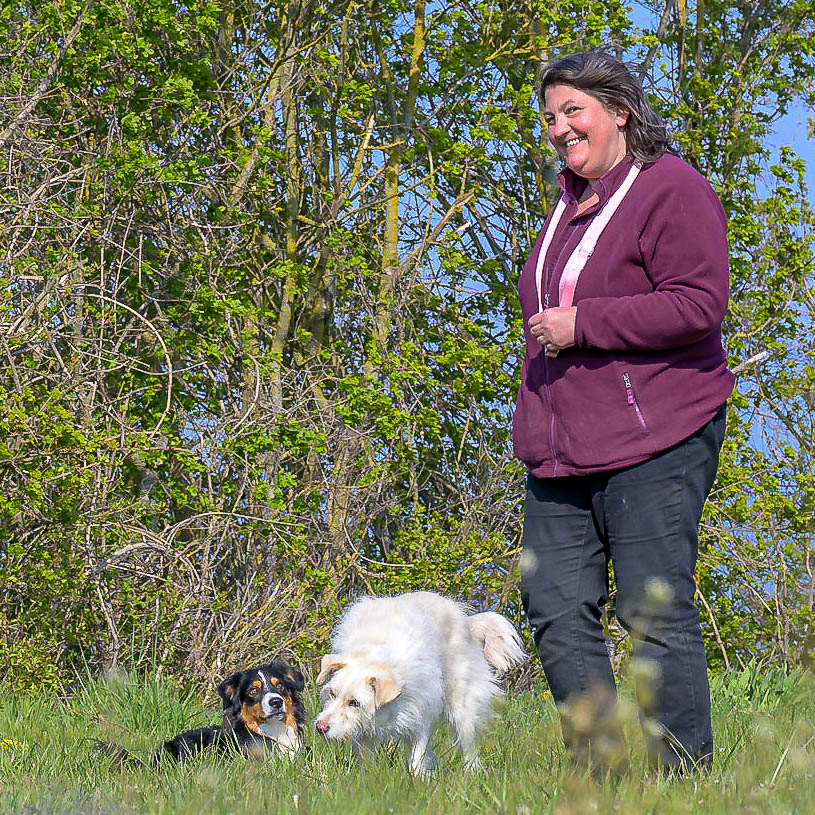 Susanne Allgeier steht mit zwei Hunden auf einer Wiese